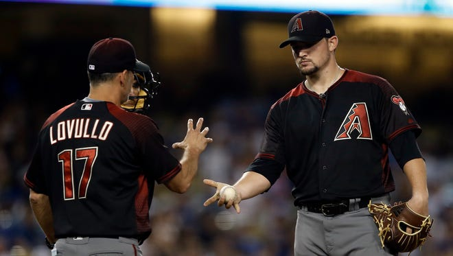 Arizona Diamondbacks manager Torey Lovullo (17) pulls starting pitcher Zack Godley, right, during a pitching change in the sixth inning of a baseball game against the Los Angeles Dodgers in Los Angeles, Wednesday, July 5, 2017.