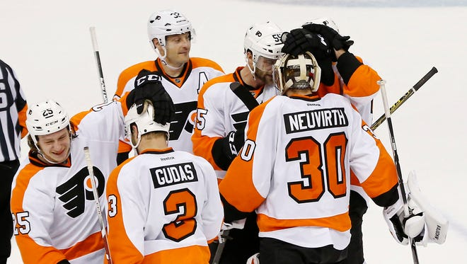 Philadelphia Flyers goalie Michal Neuvirth (30) celebrates with teammates after the Flyers game against the Washington Capitals at Verizon Center.
