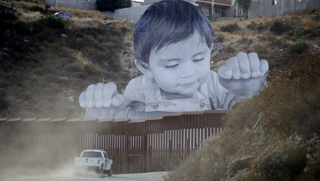 Border Patrol vehicle in front of a mural near Tecate, Calif.