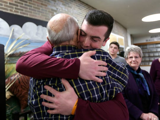 Zach McManus, senior at Marshfield High, embraces his grandfather Don Anderson after officially signing with the University of Minnesota-Duluth as a football player.