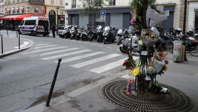 Floral tributes adorn a tree on a pavement in Paris on May 16, 2018, close to the site of a knife attack which left one dead and four injured late May 12.