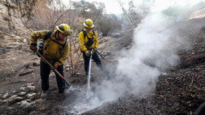 Firefighters douse hot spots from a fire Monday, Sept. 4, 2017, in the Sunland-Tujunga section of Los Angeles. (AP Photo/Ringo H.W. Chiu)
