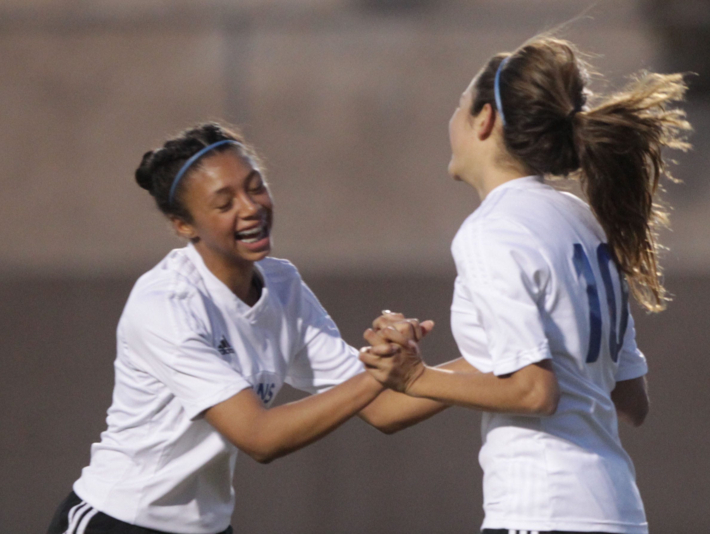 From left, Azalea Guanajuato congratulates Aylin Figueroa Uribe for scoring the third goal for Cathedral City High School during their game against Palm Desert High School on February 2, 2016.