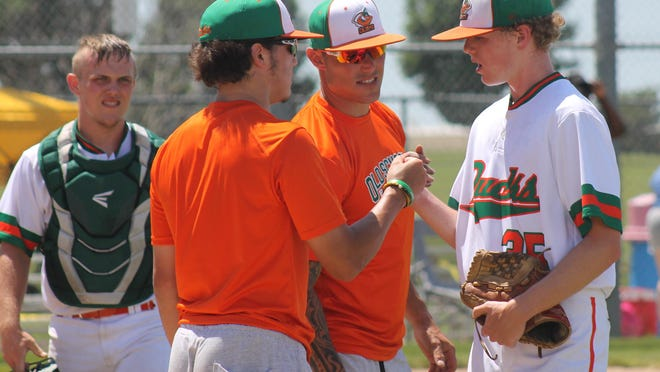 Head coach Bubby Williams, second from right, a former all-state catcher and professional player from Blue Springs, fist bumps pitcher Kole Jenks of Platte County along with his brother, assistant coach Dyllon Williams, second from left, during a recent game for his 18U Old School Baseball Ducks competitive team. Williams, after more than six seasons in pro baseball, is now trying to help players reach the next level with his 18U team while also coaching his sons in 8U and 6U.