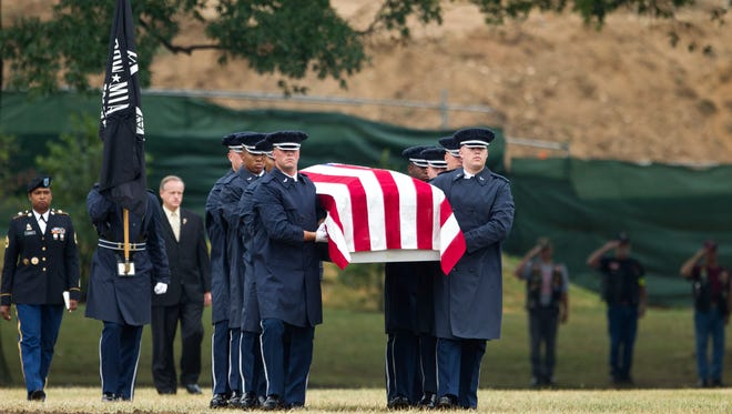 An Air Force carry team carries the casket with the remains of Air Force Col. Joseph Christiano during a burial service at Arlington National Cemetery in 2012.