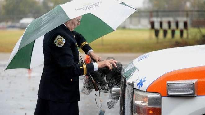 Martha Brockman attaches bows to an ambulance before Stephen Bullock's funeral Wednesday in Jackson.