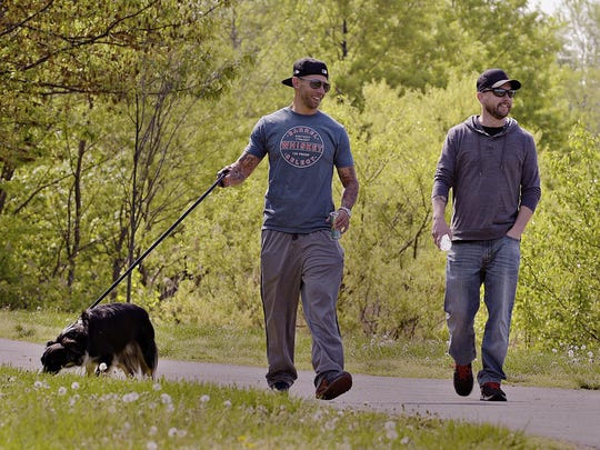 In a May 4, 2018 photo, Jason Wasylenko. left, takes a walk with his dog Harley and cousin Steve Kuc at Falls Township Community Park, Pa. Wasylenko, 32, has recently been released from his fourth stint in a state prison due to his heroin addiction. (Kim Weimer/Bucks County Courier Times via AP)