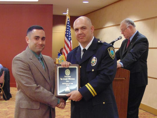 Sgt. Joseph Silberman, left, receives the Asheville Police Department's Officer of the Year award from Capt. Stony Gonce during an awards banquet Monday at the U.S. Cellular Center. At the podium is Interim Chief Steve Belcher.