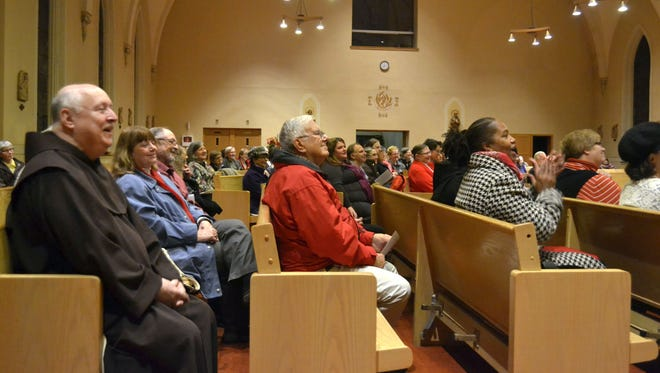 Attendees listen to the Rev. L.C. Green's sermon during the annual interfaith Thanksgiving worship service at St. Mary of the Angels Parish in Green Bay on Nov. 24, 2015.