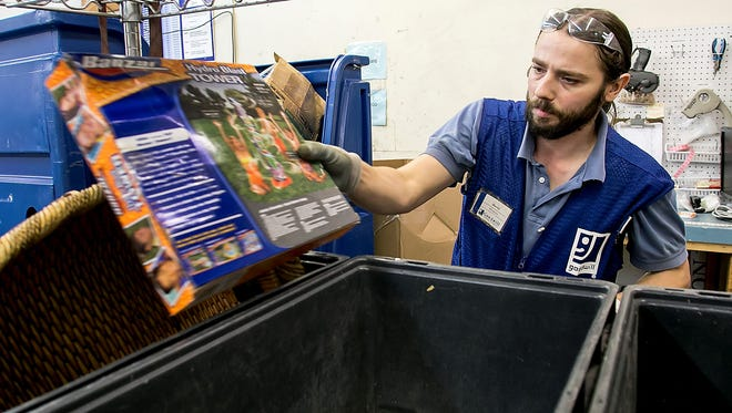 Goodwill employee Daniel Richardson places a donated item into a pricing bin.