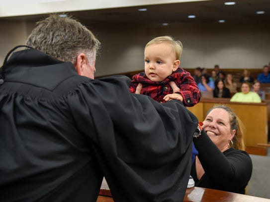 Circuit Judge Duane Slone reaches to pick up 1-year-old