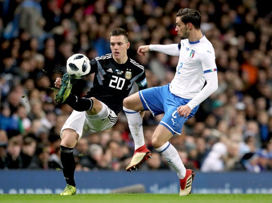 Argentina's Giovani Lo Celso, left, and Italy's Mattia De Sciglio battle for the ball during the international friendly soccer match between Argentina and Italy at the Etihad Stadium in Manchester, England, Friday, March 23, 2018.   (Martin Rickett, PA via AP)