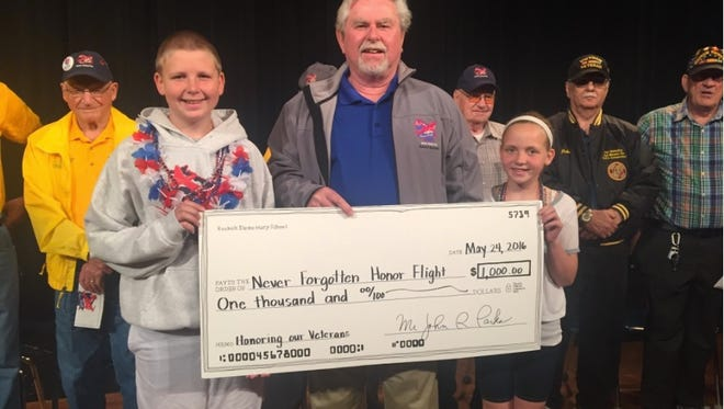 Eli Trzinski, left, and Sarah Trzinski, right, present a check for $1,000 to Jim Campbell, co-founder of The Never Forgotten Honor Flight.