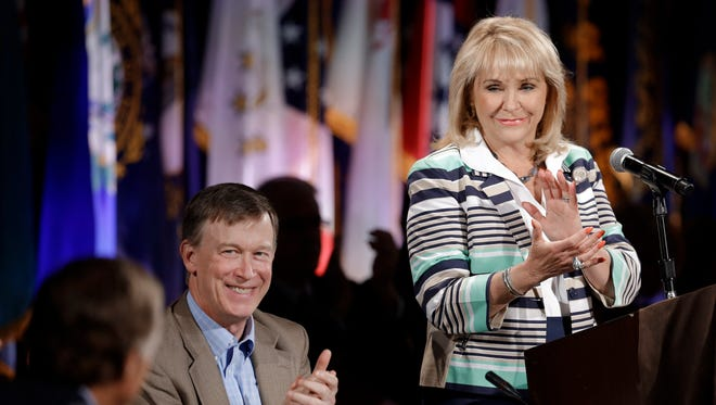 Oklahoma Gov. Mary Fallin, right, and Colorado Gov. John Hickenlooper, center, applaud Tennessee Gov. Bill Haslam, left, during the closing session of the National Governors Association convention Sunday, in Nashville, Tenn.
