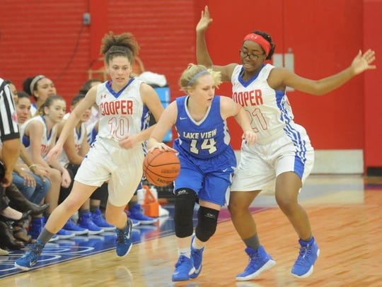 Cooper's Cheyenne Sherwood, left, and Daniece Edwards, right, put pressure on San Angelo Lake View's Bryce Crabtree in the second quarter of a game Feb. 2 at Cougar Gym.