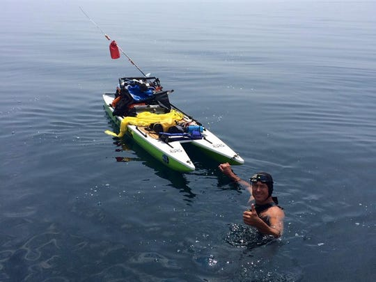 Dr. Chris Lechner, 54, swam more than 80 miles across Lake Michigan over the weekend, pulling behind him a paddleboard with food and safety gear on it.