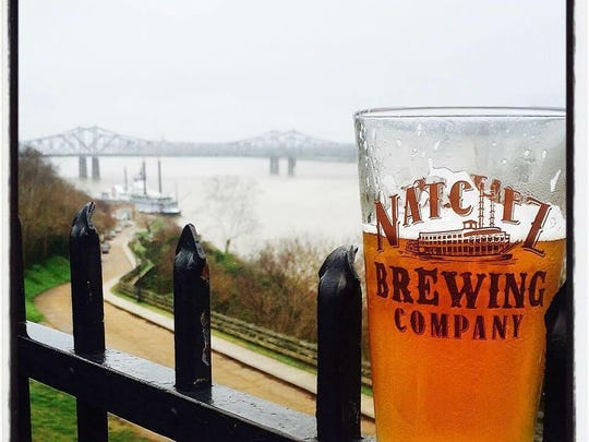 A drink in a Natchez Brewing Company Glass overlooks the Mississippi River in the historic city.
