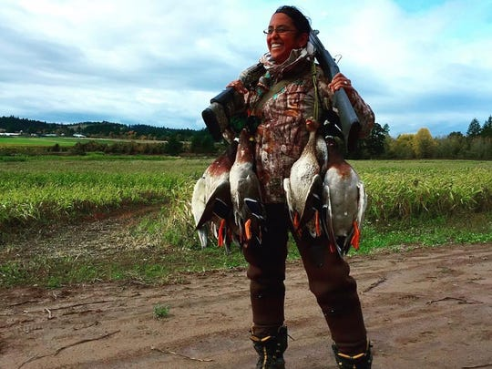 Asha Aiello poses with a strap full of ducks from a good day hunting a flooded corn field in the Willamette Valley.