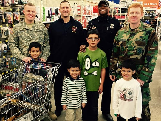 The Sanchez brothers of Fond du Lac, from left, Rudy, Dyland, Amadeo and Yandel are joined by U.S. Army National Guard Sgt. Cody Bowe, Fond du Lac Fire Department Paramedic Jack Prall, Fond du Lac Police Officer Keywon Brown and U.S. Air Force Senior Airman Shawn Provot for an afternoon of shopping at Fleet Farm last month.