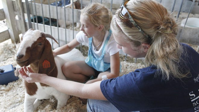 Brooklyn Bauer and Cheyenne Trammell,  both 4-H members were keeping Cheyenne's Boer goats company in the pen.