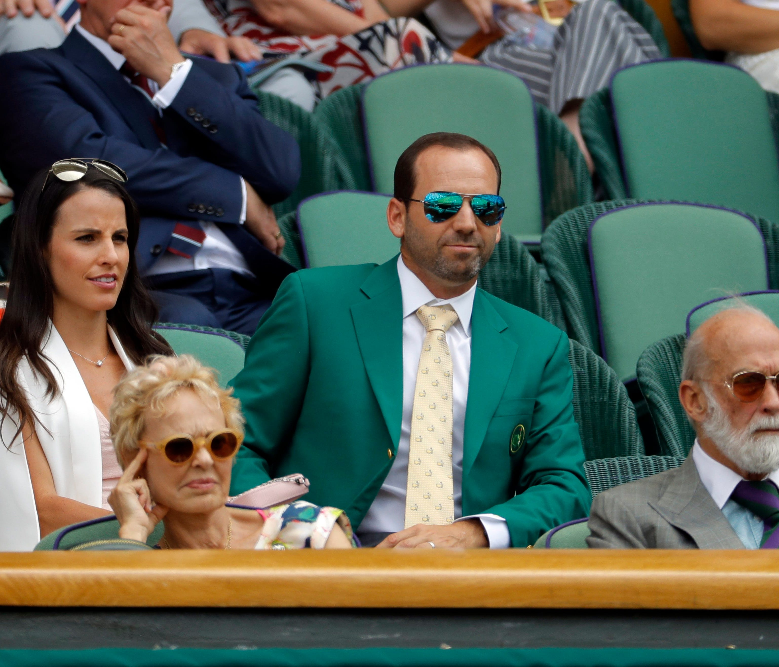 Golfer Sergio Garcia, wearing his green Masters jacket, centre and fiancee Angela Akins sit in the Royal Box on day five at the Wimbledon Tennis Championships in London Friday, July 7, 2017. (AP Photo/Alastair Grant)