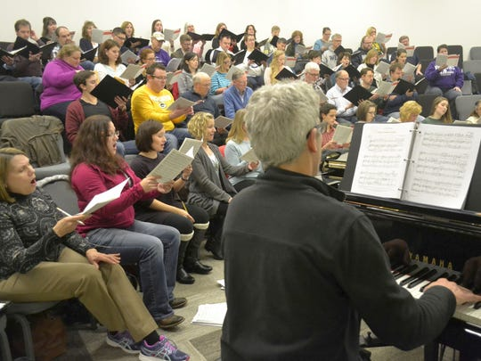 As the Rev. Dan Dinkler plays organ, members of the newVoices choir sing during a rehearsal at Appleton Alliance Church on Sunday night, Dec. 4, 2016, for their upcoming Christmas concerts in Green Bay and Appleton.