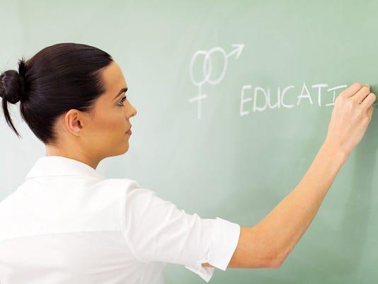 educator writing sex education on chalkboard