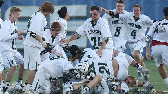 Yorktown players pile onto teammate Dom Cijoffi (26) after he scored the game winning goal in overtime to defeat Garden City 5-4 to win the boys state lacrosse semifinal at SUNY Albany June 7, 2017.