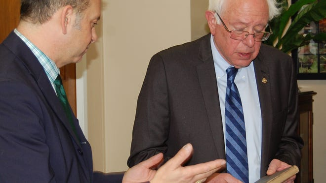 """Neil Glick, left, a book collector from Washington, D.C., presents """"The Glory and The Shame of England"""" to Sen. Bernie Sanders, I-Vt., in Washington."""