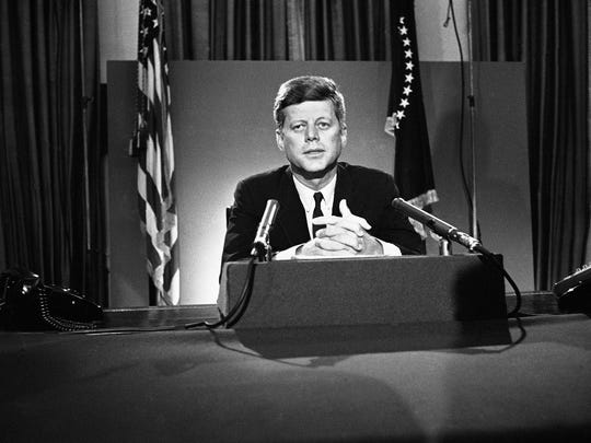 U.S. President John F. Kennedy sits behind microphones at his desk in Washington after finishing his radio-television broadcast to the nation on the nuclear test ban agreement initialed by negotiators in Moscow.