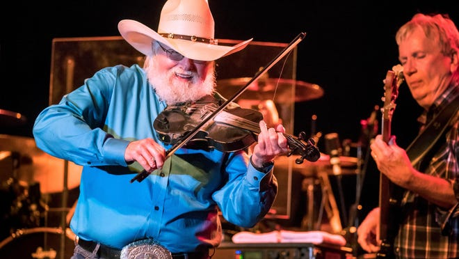 "Charlie Daniels saws away on a fiddle as the Charlie Daniels Band headlines on the Peoria Riverfront in 2018. Daniels is most famous for ""The Devil Went Down to Georgia,"" along with several other fiddle-led tunes. He died Monday morning, according to his publicist."