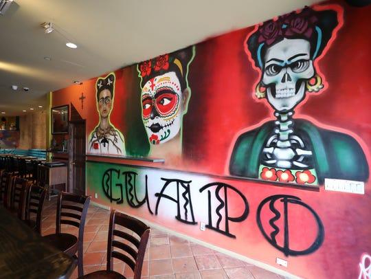 Painted hip artwork adorns the walls of Guapo Cocina