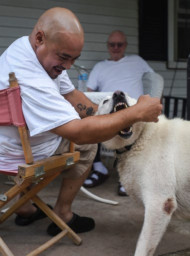 Angel Correa, known by his formal Buddhist name Rahula, plays with Huey, a five-year old American German Shepard, while relaxing with John Mulligan, known by his Buddhist name Sivili, outside Bodhi House on Aug. 3, 2014 in Mount Joy Township.