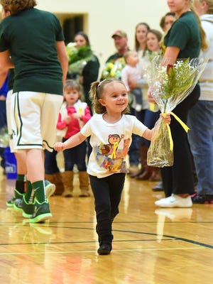 """One of several, Raygan Batton, 3, runs across the gymnasium with flowers she received after being recognized for her personal fight against cancer. Wilson Memorial High School hosted their """"Plays for the Cure"""" cancer awareness night at their girls' basketball game against Riverheads played in Fishersville on Friday, Jan. 30, 2015. Raygan currently has no evidence of the disease presenting itself and is checked every three months."""