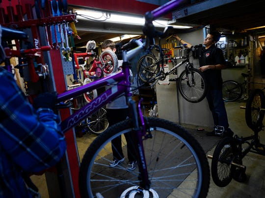 Clark Evanitus, Ben Kelli, and Derrick Rorrer tune up bikes at Gung Ho Bikes last year. They're continuing the tradition this year volunteering their time to fix up donated bikes before giving them away to local charities.