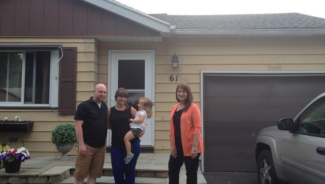 From left, Chris and Jackie Guck, their daughter Abigail, and their Realtor Sandra Maluta stand in front of the city home the Gucks just sold to a first-time buyer.