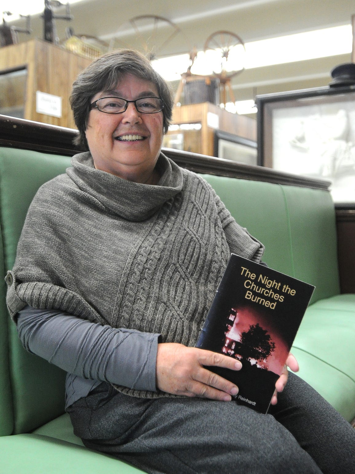 """Tracy Reinhardt holds her book, """"The Night the Churches"""