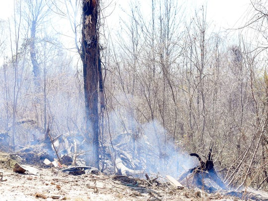 Trees and brush continue to smolder Tuesday at the site of a house fire on 123 Halford Lane near Yazoo City.