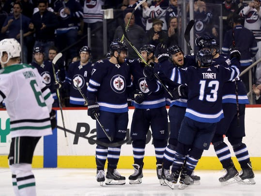 Winnipeg Jets' Adam Lowry (17), Joel Armia (40), Ben Chiarot (7), Brandon Tanev (13) and Tyler Myers (57) celebrate after Chiarot scored against the Dallas Stars during the second period of an NHL hockey game Sunday, March 18, 2018, in Winnipeg, Manitoba. (Trevor Hagan/The Canadian Press via AP)