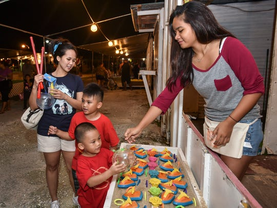 Luke Estoy, 3, of Dededo, inspects his new jelly ball prize given by Lizel Dela Cruz at the Liberation Carnival in Tiyan. Luke earned his treasure by choosing a winning jet-ski from the table.