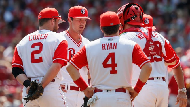 Cincinnati Reds starting pitcher Tyler Mahle, second from left, reacts as he meets on the mound with his teammates after giving up a two-run double by Pittsburgh Pirates' John Jaso in the fourth inning of the game Sunday, Aug. 27, 2017, in Cincinnati.