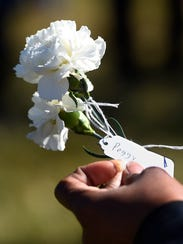 A visitor looks at the name tag on a flower that was laid at the memorial for a person who once was enslaved at the Hermitage.