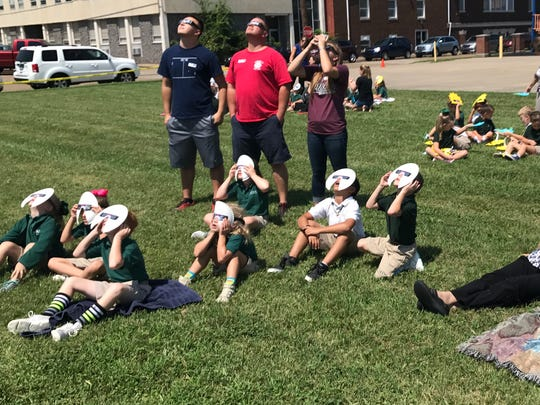 Holy Name School students, staff and visitors look up at the solar eclipse on Aug. 21, 2017.