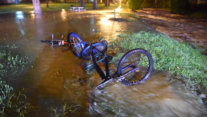 Water flows under a pair of abandoned bicycles next