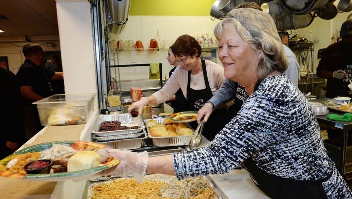 Volunteer Julie Rich hands a plate to another volunteer at the Fort Collins Rescue Mission's annual Great Thanksgiving Banquet on Monday, November 21, 2016.  An activist group is working on pairing Fort Collins residents with volunteer opportunities for the March 25 Women's Day of Service.