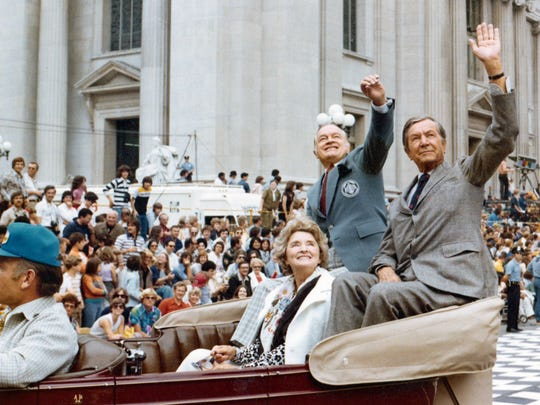 Bob Hope and Tony Hulman wave to fans during the 1976 Indianapolis 500 Festival Parade. Hope's wife, Dolores, rides along.