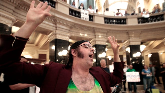 Brandon Barwick of Madison joins Solidarity Sing Along participants in the rotunda of the state Capitol in Madison in September 2012.