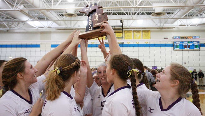 The Bronson High School volleyball team holds up their regional trophy after beating Kalamazoo Christian Thursday evening