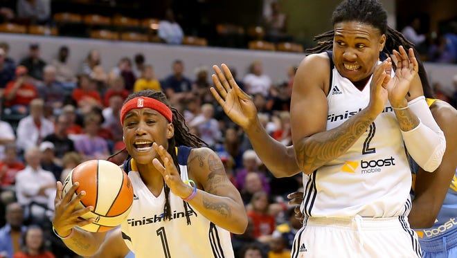 Indiana Fever guard Shavonte Zellous grabs a rebound as forward Erlana Larkins attempts to get out of the way against the Chicago Sky inside Bankers Life Fieldhouse, on Saturday, August 16, 2014, in Indianapolis.