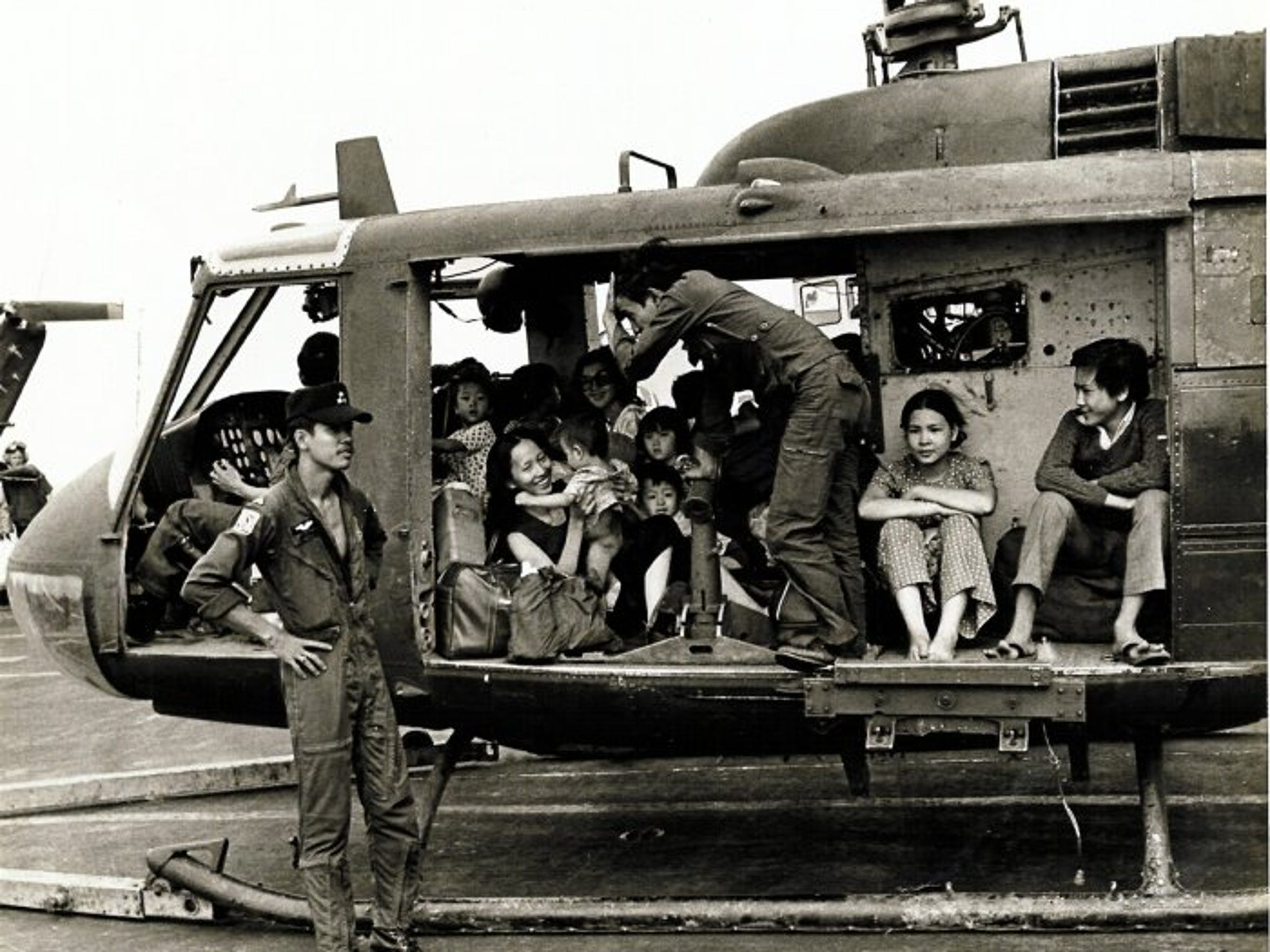 Vietnamese refugees sit in a helicopter on the USS